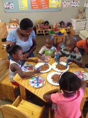 Teacher Maria works with three year olds on developing fine motor skills.