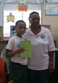 A student poses with his copy of the Butterfly Storybook, distributed by the Jamaican Reading Association