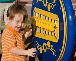 A young child enjoys the Centennial Playground.