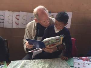 Rotarian Peter Johnson reading with a student in Guatemala.
