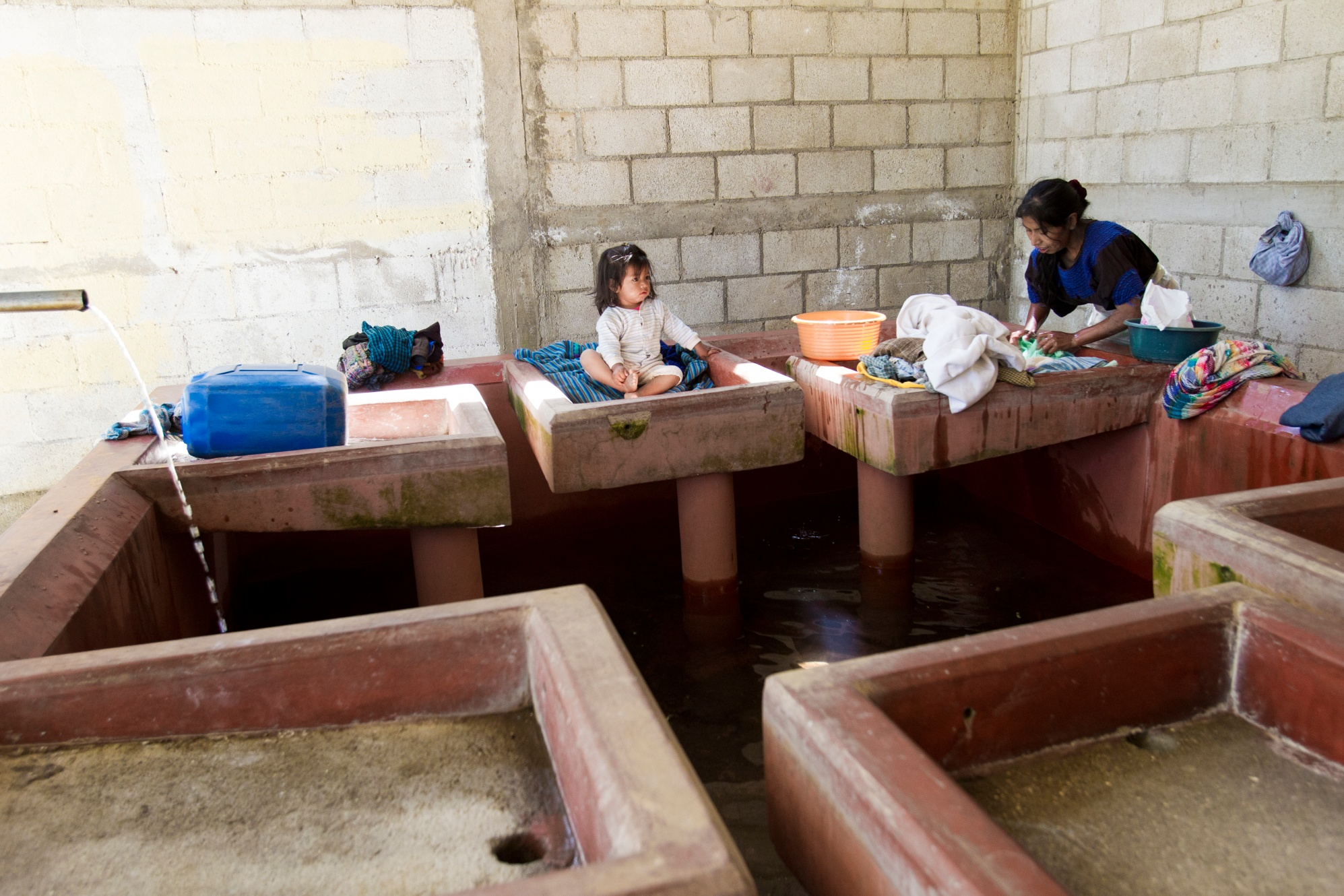 A woman washes clothes at a public laundry facility near El Tunino school in Sumpango, Guatemala. El Tunino is one of nine schools in the Sumpango area at which Rotary is improving water and sanitation facilities. It now has clean water, new hand washing stations, toilets, septic tanks, and drainage systems.