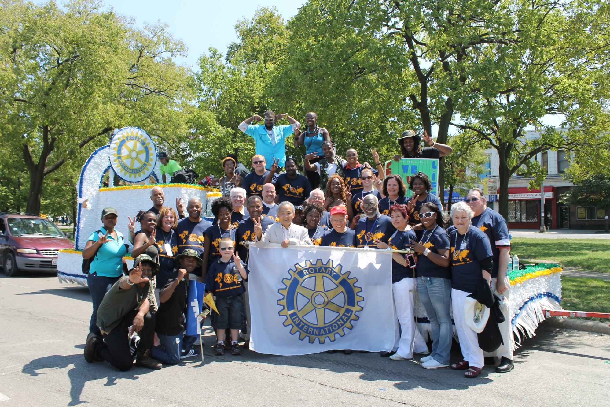 Rotarians attend the Bud Billiken parade to help spread the word about Peace Summits. Past RI President Tanaka is in front in a red hat!