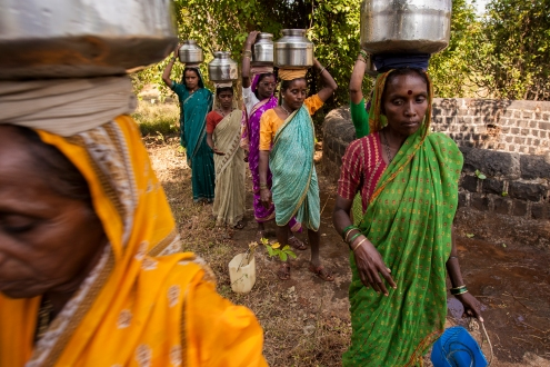 Women carry their daily water supply from a well near the village of Vihule Kond, Maharashtra, India.
