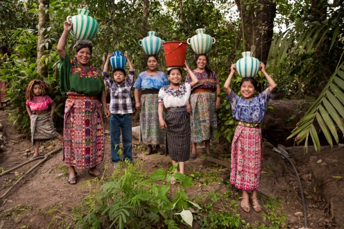 Women and children in Sacala Las Lomas, Guatemala carry water to and from the community well to their homes.