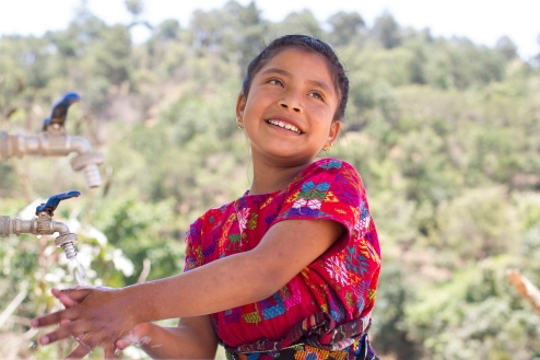 Maria, 8 yrs., fills her cup with clean drinking water at El Tunini school in Guatemala.