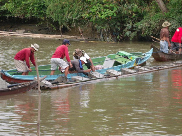 Members of the Rotary Community Corps make the river crossing with the help of anchors.