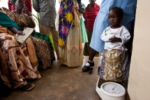 A young girl is weighed while waiting to see a doctor.