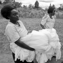 A group of women carry moquito netting to their tailoring class. The class, which provides women with a vocational skill, also provides cheap school uniforms and mosquito nets for community members.