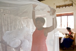 Deborah Lubega, one of the tailoring class teachers prepares, mosquito netting to be sewn. The class, which provides women with a vocational skill, also provides cheap school uniforms and mosquito nets for community members.