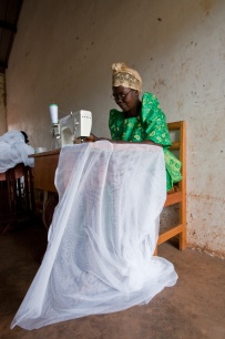Joweriya Kigundu, a tailoring student, sews sheets of mesh to make mosquito nets. The class, which provides women with a vocational skill, also provides cheap school uniforms and mosquito nets for community members. .