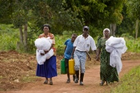 Community volunteers and a Rotarian from the Rotary Club of Muyenga, Ugandacarry new mosquito nets and jerry-cans of water to a site where they can treat the nets with a chemical repellent.