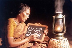"""A women traces letters on a slate. The Rotaract Club of Sullurpet, India, developed an adult literacy program to teach 40 people in that community to read and write. Appeared in """"The Rotarian,"""" April 2002, page 22. 2000-2001 Photo Contest, Rotary Programs, 1st place, Photographer: Sunkara Harish."""
