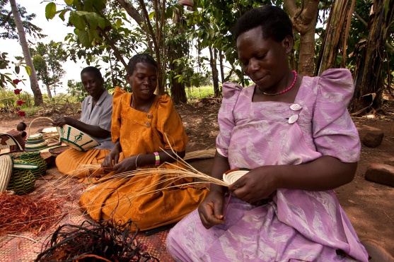 A member of a local women's handicraft group in Mpigi District, Uganda, adds a decorative strip of raffia to the basket she is weaving.