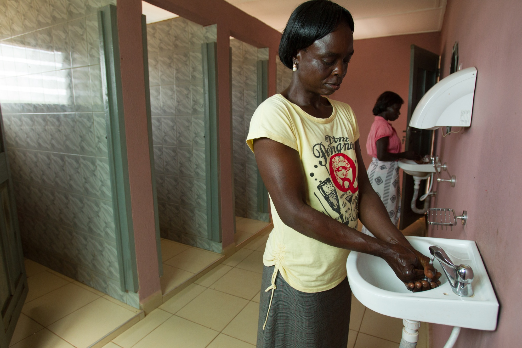 Women wash their hands in the Rotary-funded toilets at the local market in Sunyani, Ghana. The toilets were built to improve sanitation and prevent the spread of bacterial diseases.