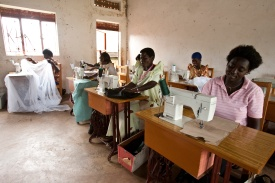 Women work on projects during a tailoring class. The class teaches women a vocational skill, and provides cheap school uniforms and mosquito nets for community members.