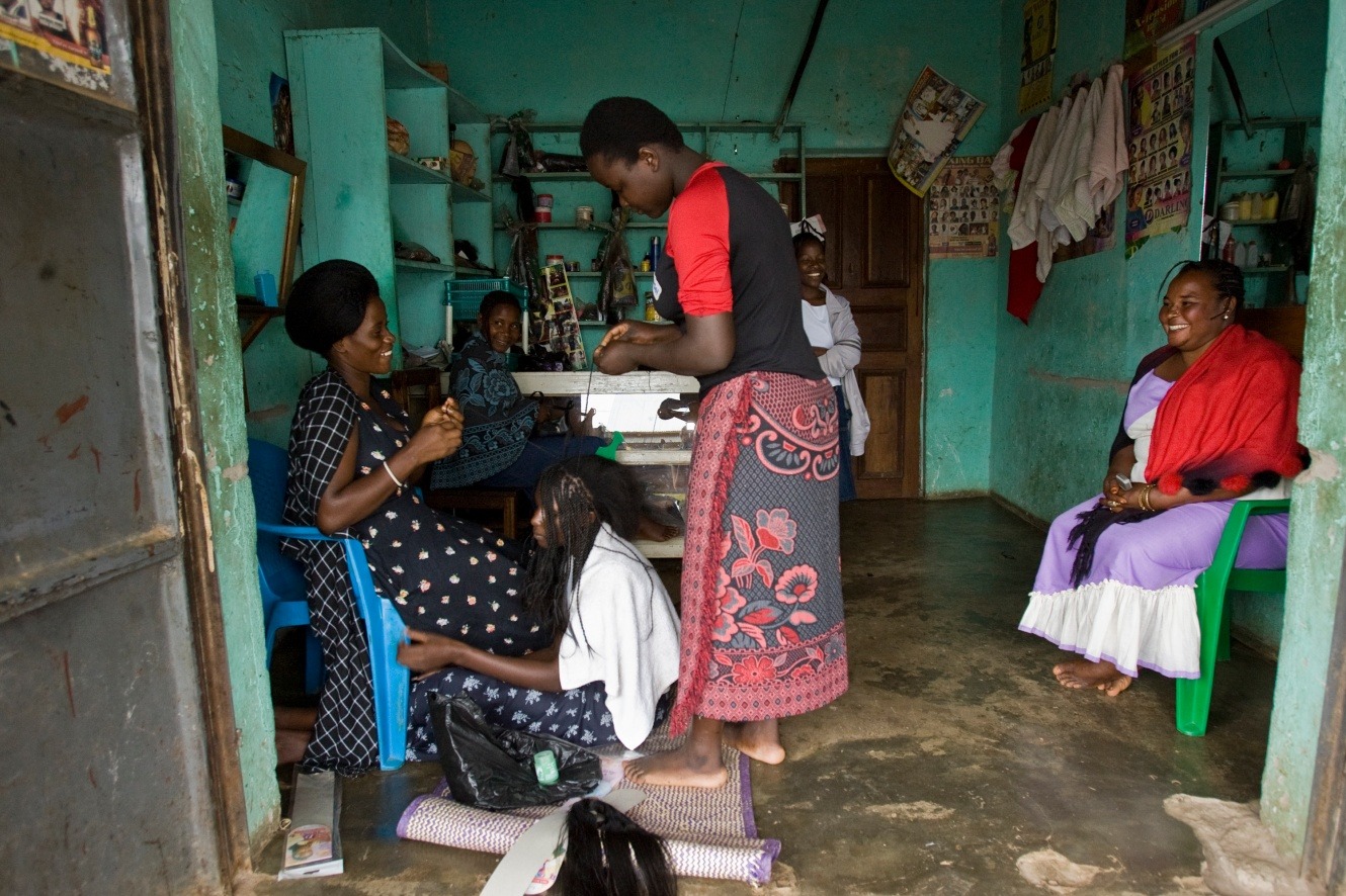 Hairdressing student Nassolo Bena (right foreground) helps her teacher braid a girl's hair, a process that can take hours, during a lesson in Kalisizo, Uganda.