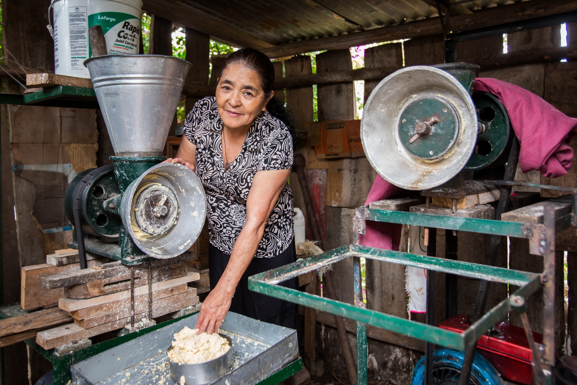 Maria Higinia Reyes mills corn in Zacate Blanco, Honduras. She takes part in an Adelante Foundation program supported by a Rotary global grant, in which women in rural Honduras get group borrowing opportunities and business training aimed at increasing their household incomes.
