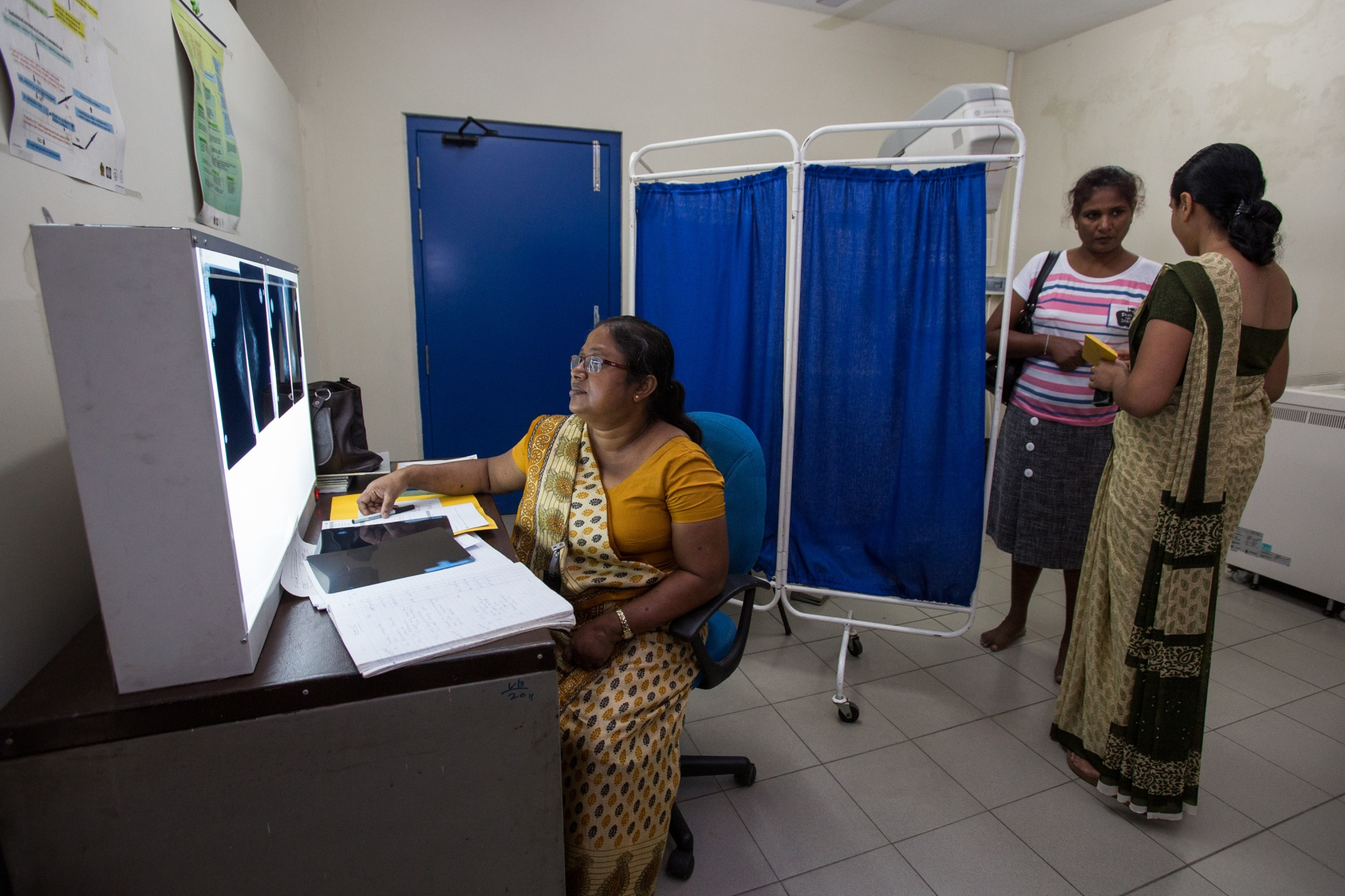 Radiologist Jayantha Mapatona (left) reviews mammogram results at the Cancer Prevention and Early Detection Centre in Colombo, Sri Lanka.