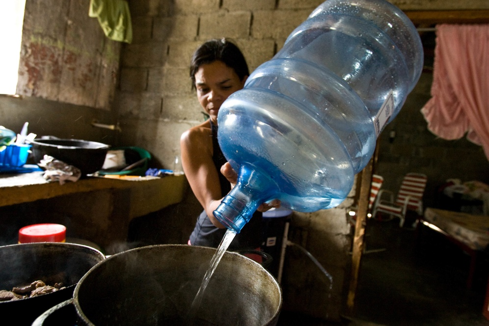 Maria Magdalena Gonzalez cooks with water purified by a bio-sand filter in her home in Bonao, Dominican Republic.