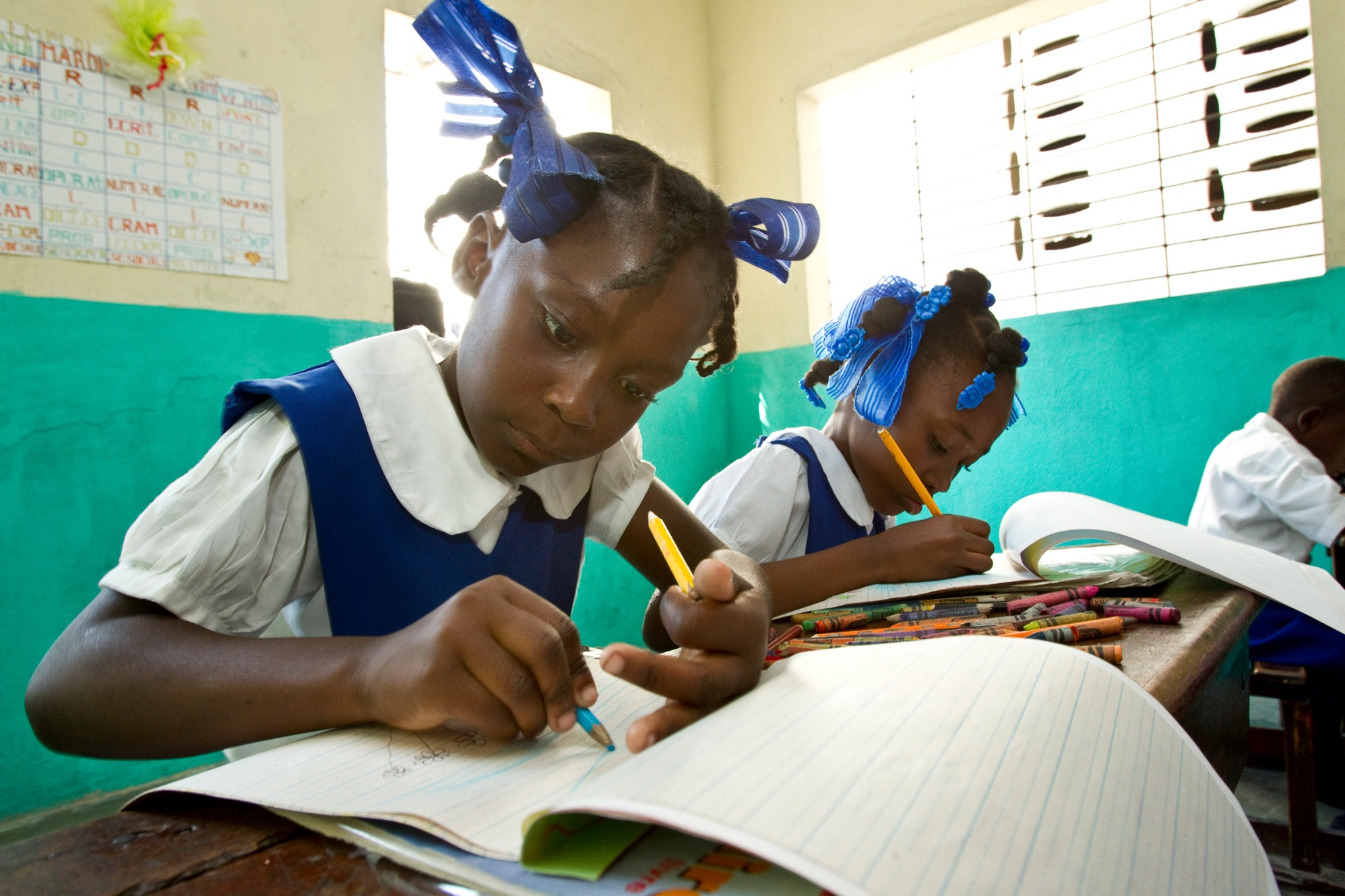 Students at Sainte Famille elementary school in Cayes, Haiti, draw pictures. The school was rebuilt after the 2010 earthquake in Haiti using funds donated to The Rotary Foundation's Haiti Earthquake Relief Fund.