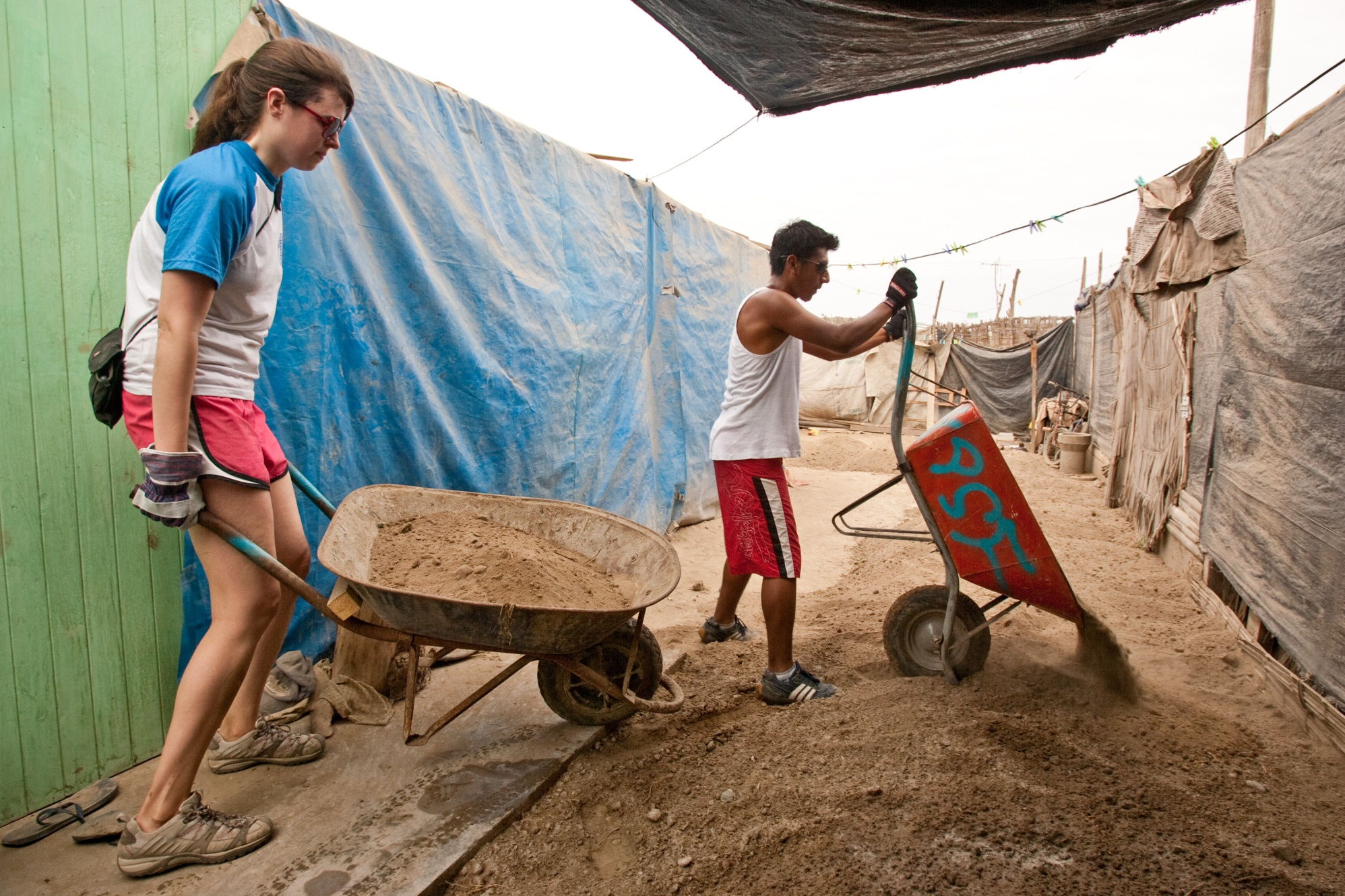 Northwestern University Rotaractor Lauren Coffaro (left) and Pisco Rotaractor Jassu Zamudio dump sand that will be used to build new latrines in El Molino, Peru. Members of the Rotaract Club of Northwestern University, Illinois, USA, are volunteering with Pisco Sin Fronteras, a local organization that provides sustainable disaster relief and rebuilds local communities, during a spring break service trip to Pisco, Peru.