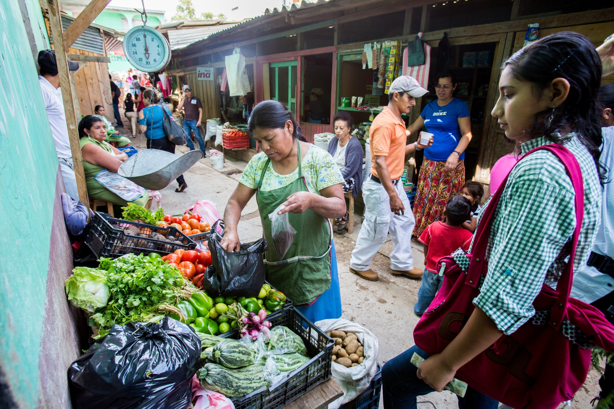 Adelante Foundation microcredit client Dona Ninfa (center) sells vegetables at the market in La Esperanza, Honduras. The Adelante Foundation's microcredit program, which offers women loans and business training aimed at increasing their household incomes.