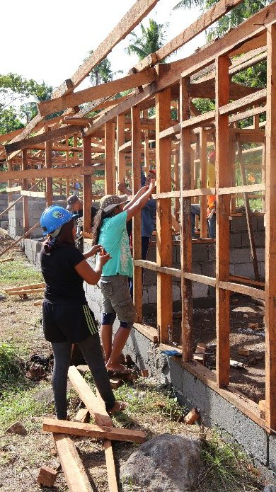 Workers building transitional homes. The green roofing sheets were provided by ShelterBox.