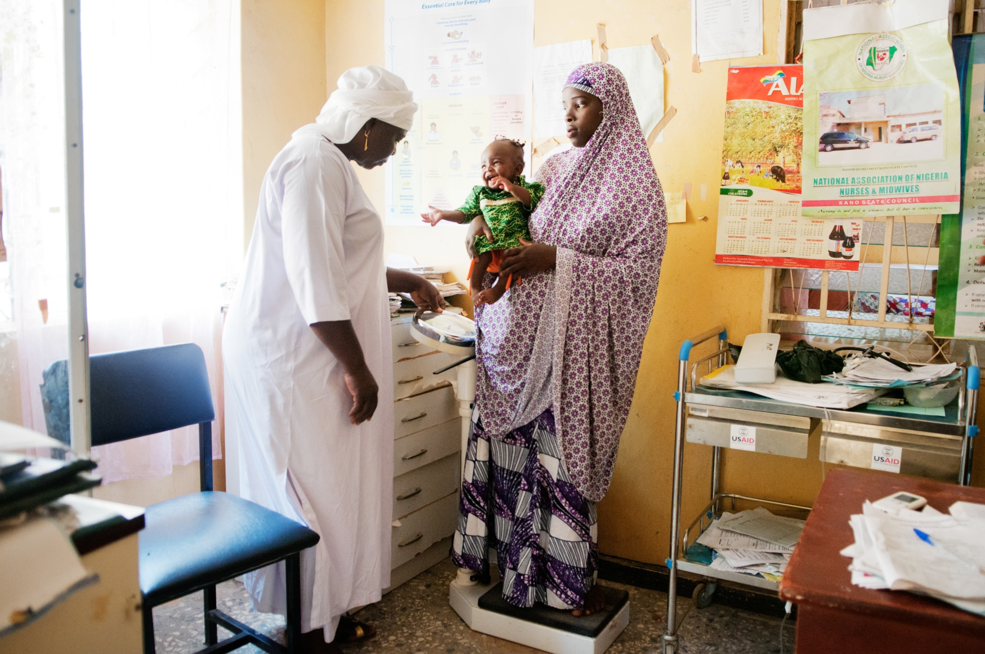 Midwife Tamar Okoh (left) weighs Azima Yahaya and her child Aisha at Sumaila General Hospital in Sumaila, Kano State, Nigeria. With no scale for toddlers at the hospital, she will have to calculate the difference between the weight of the mother and child. 4 September 2015. The Rotarian Action Group for Population and Development (RFPD) has supported work to advance maternal and child health in Nigeria for nearly 20 years.