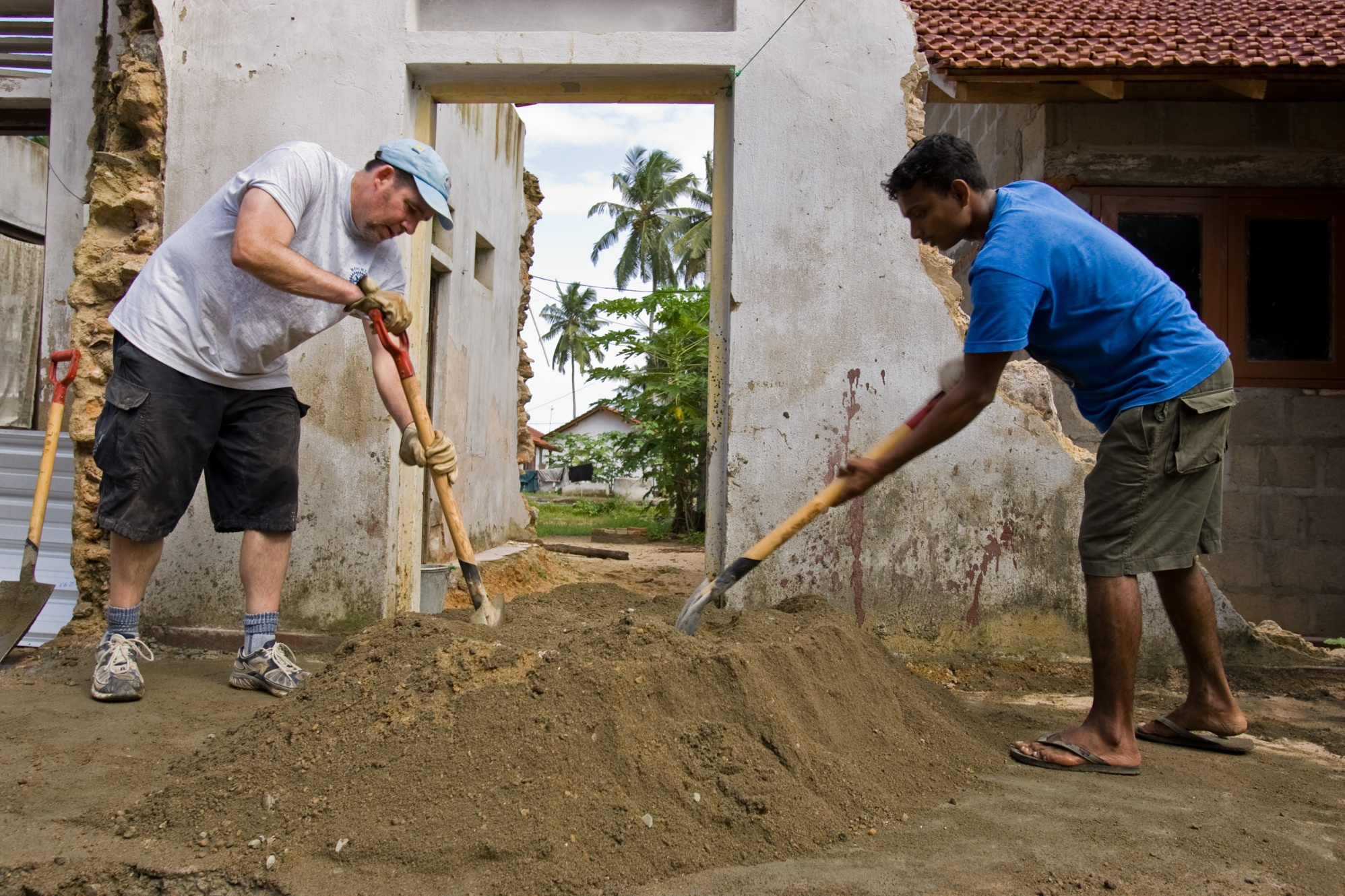 A member of the Rotary Club of Rockland, Maine, USA, and a local worker mix concrete at a construction site in Sri Lanka. Eleven members of the club traveled there to rebuild homes destroyed by the 2004 tsunami. They worked with Habitat for Humanity's Global Village program, in which international volunteers, homeowners, and local volunteers build homes together.