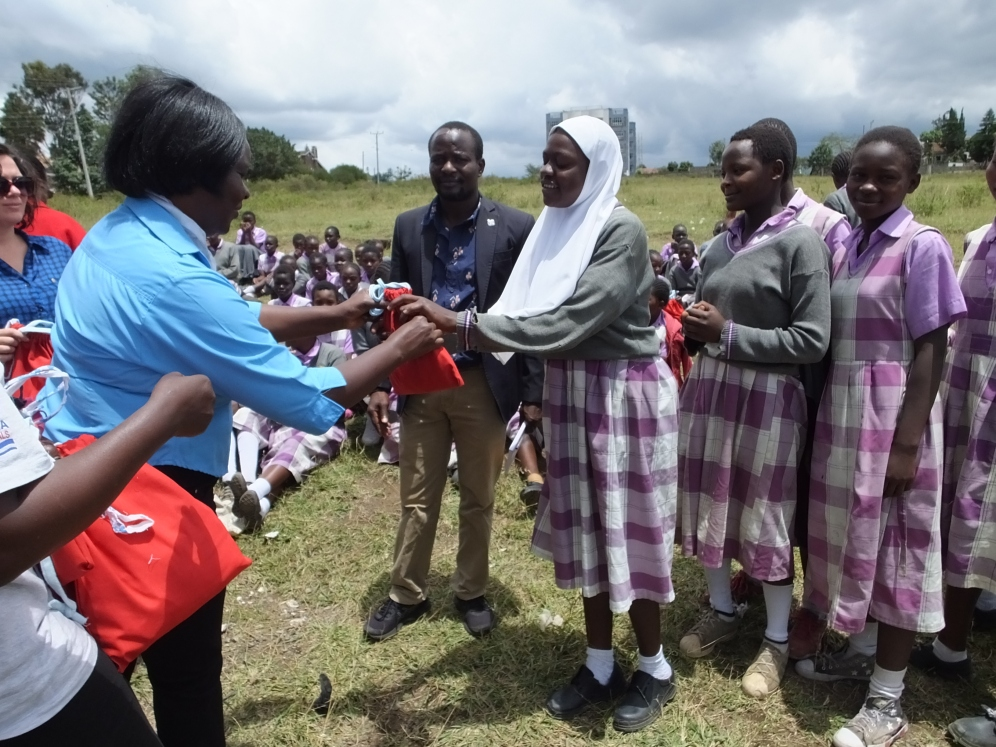 Dr Tsimbiri giving a schoolgirl a bag containing 8 reusable sanitary pads, soap, and a washcloth.
