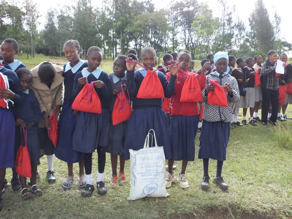 Schoolgirls shyly displaying their new Rotary bags of supplies.